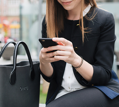 Woman sitting next to purse and holding cell phone.