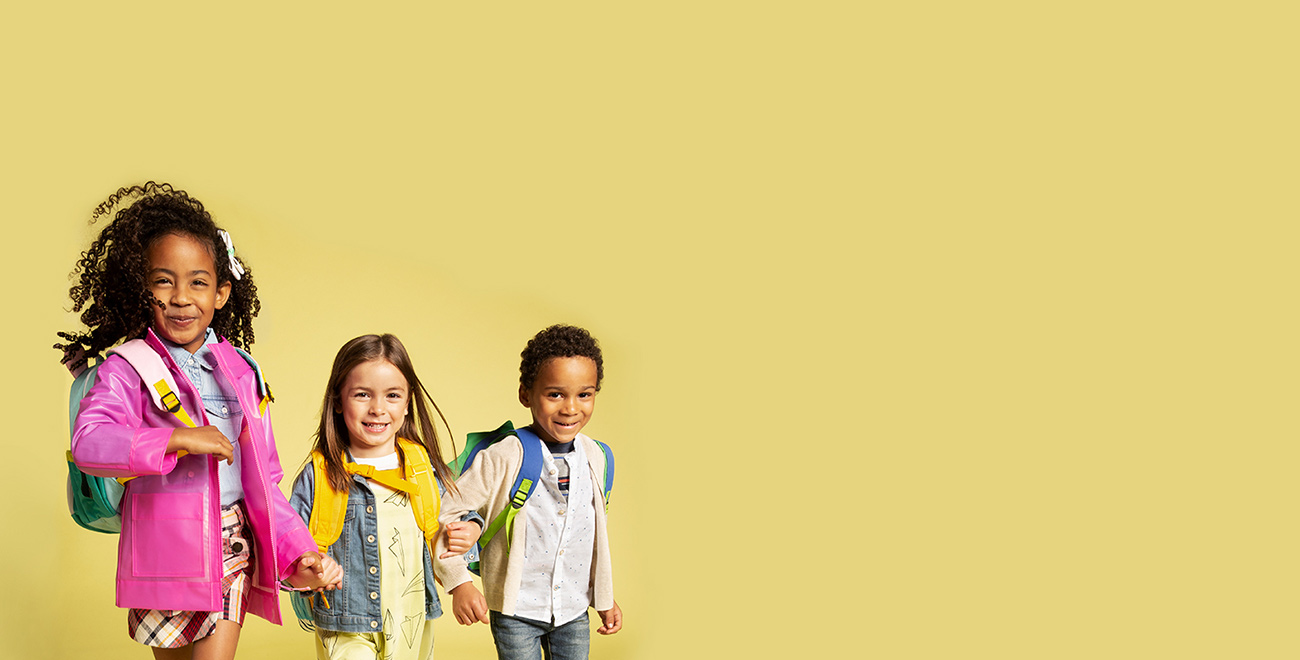 Three smiling schoolkids arm-in-arm wearing backpacks