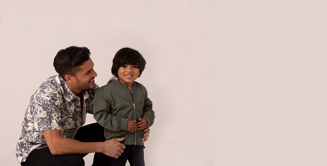 Father wearing a floral print short-sleeve shirt posing with his happy son, who is wearing a jacket.