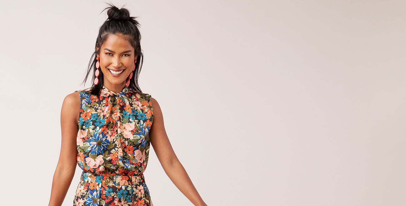 A smiling woman wearing a floral dress