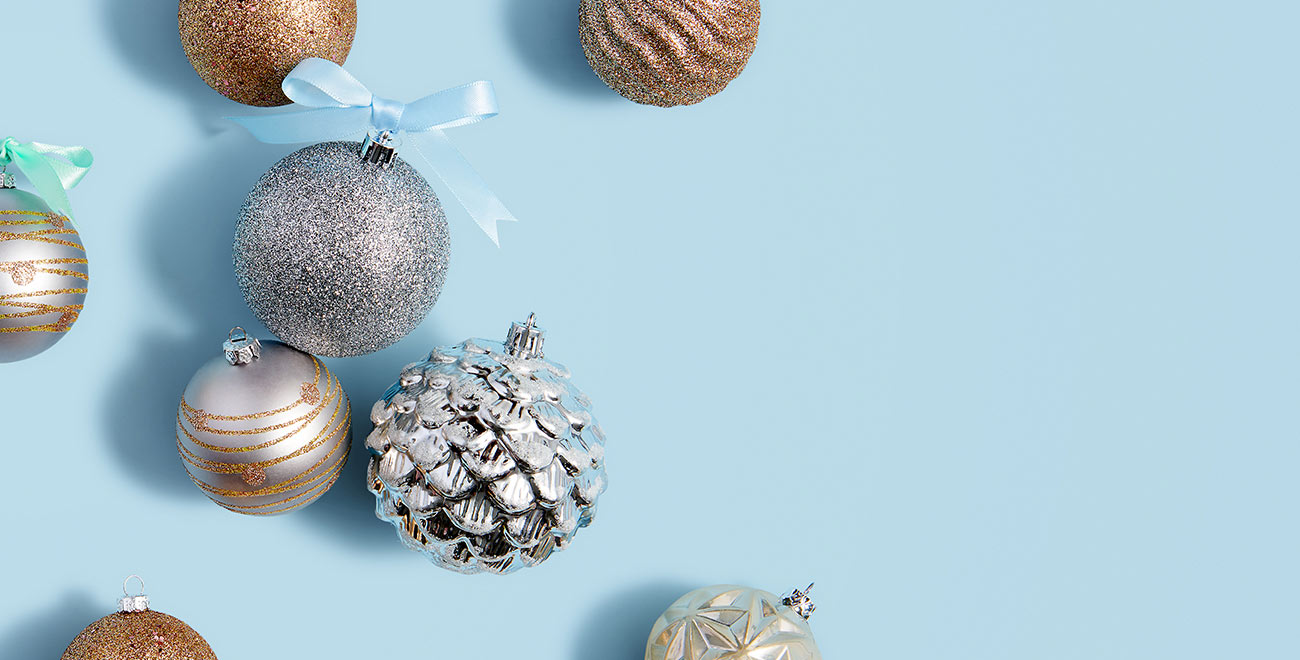 Metallic holiday ornaments on a blue background