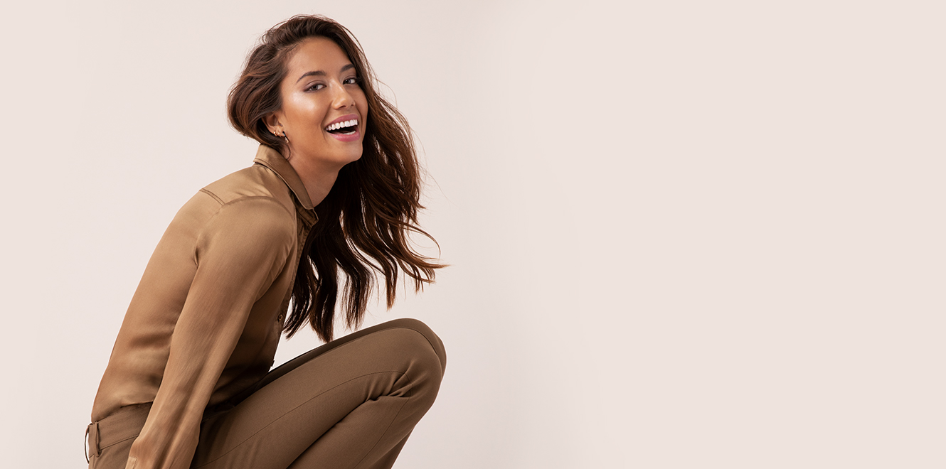 Smiling woman in a tan blouse and brown pants crouching down
