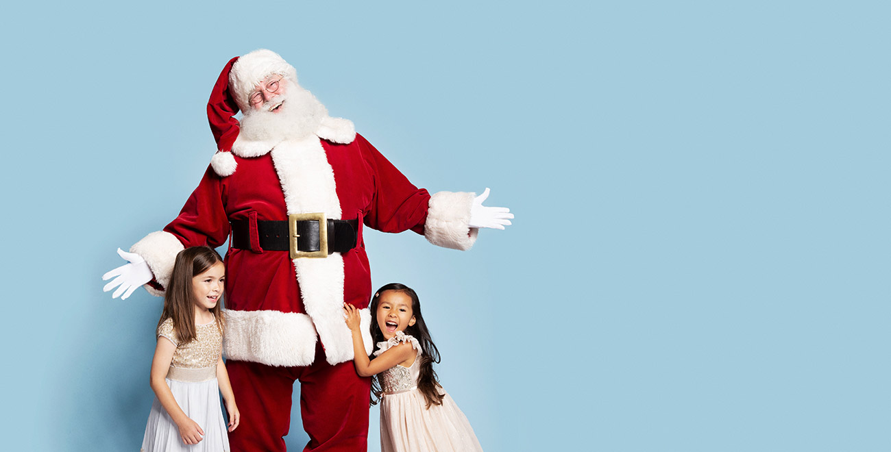Two girls hugging Santa