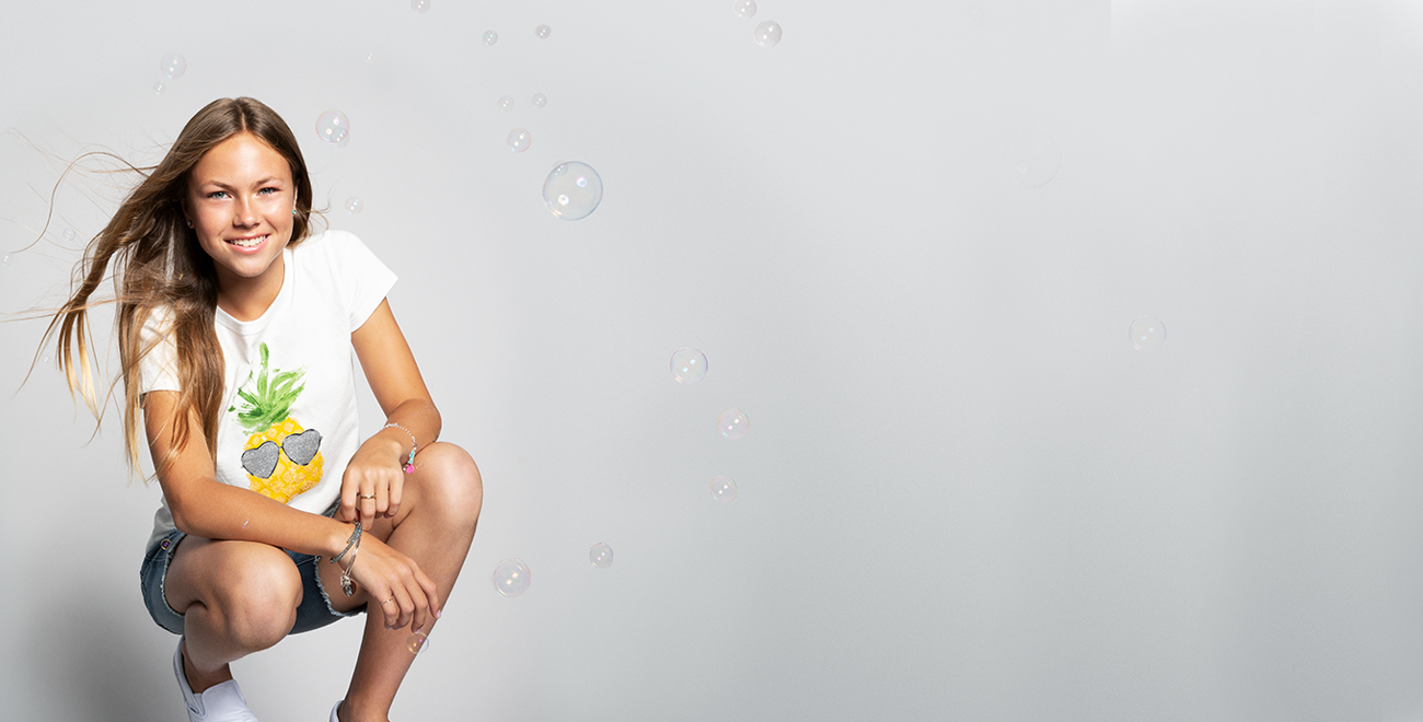 Young woman wearing a t-shirt and shorts crouching down and surrounded by bubbles
