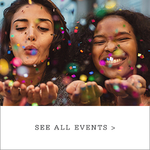 Image of two young women blowing confetti out of their hands.