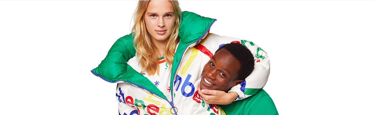 2 smiling models embraced in side hug while wearing Benetton apparel