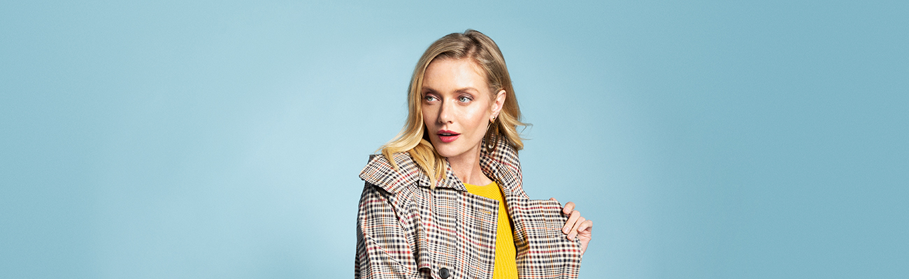Blonde woman wearing a yellow sweater and plaid trench coat