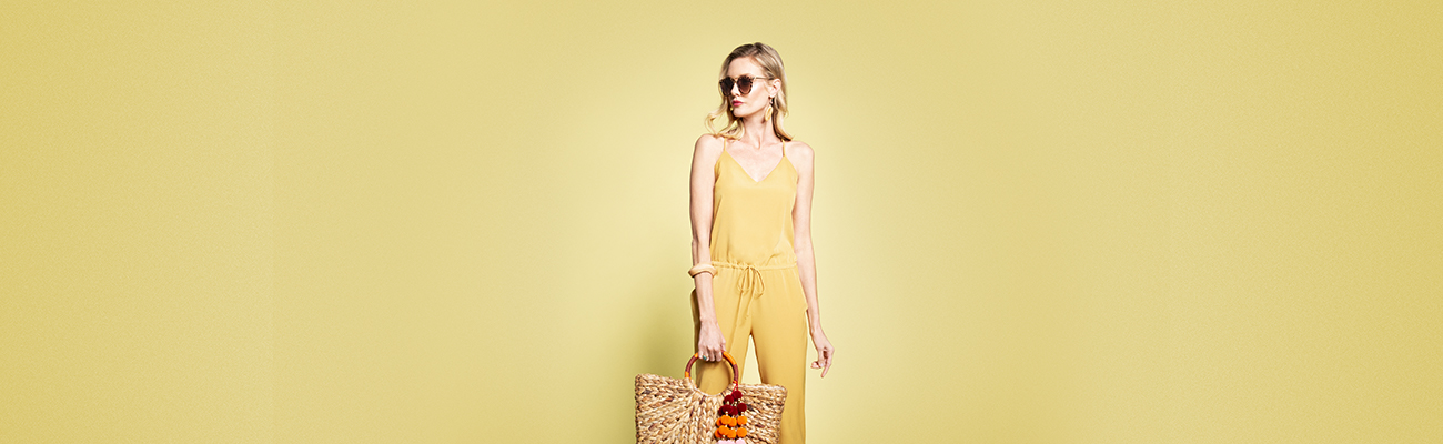 Woman wearing sunglasses and a yellow summer jumpsuit, carrying a rattan bag, against a yellow background