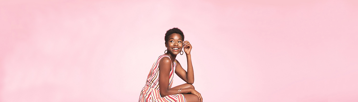Young woman crouching down wearing a striped sundress against a pink background