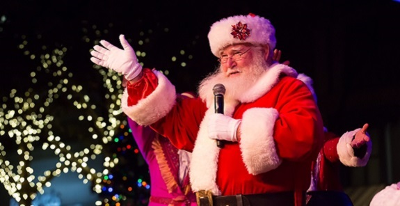 Santa Claus waving to the crowd as he talks into a microphone.