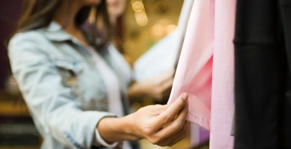 Woman touching some clothing at a store.