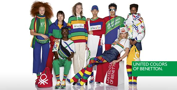 8 models wearing multicolored patterns of red, green, blue and yellow of Benetton apparel.