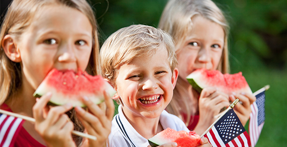 Three young children eating watermelon and holding American flags