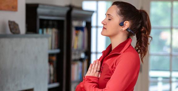 Image of woman doing yoga wearing headphones