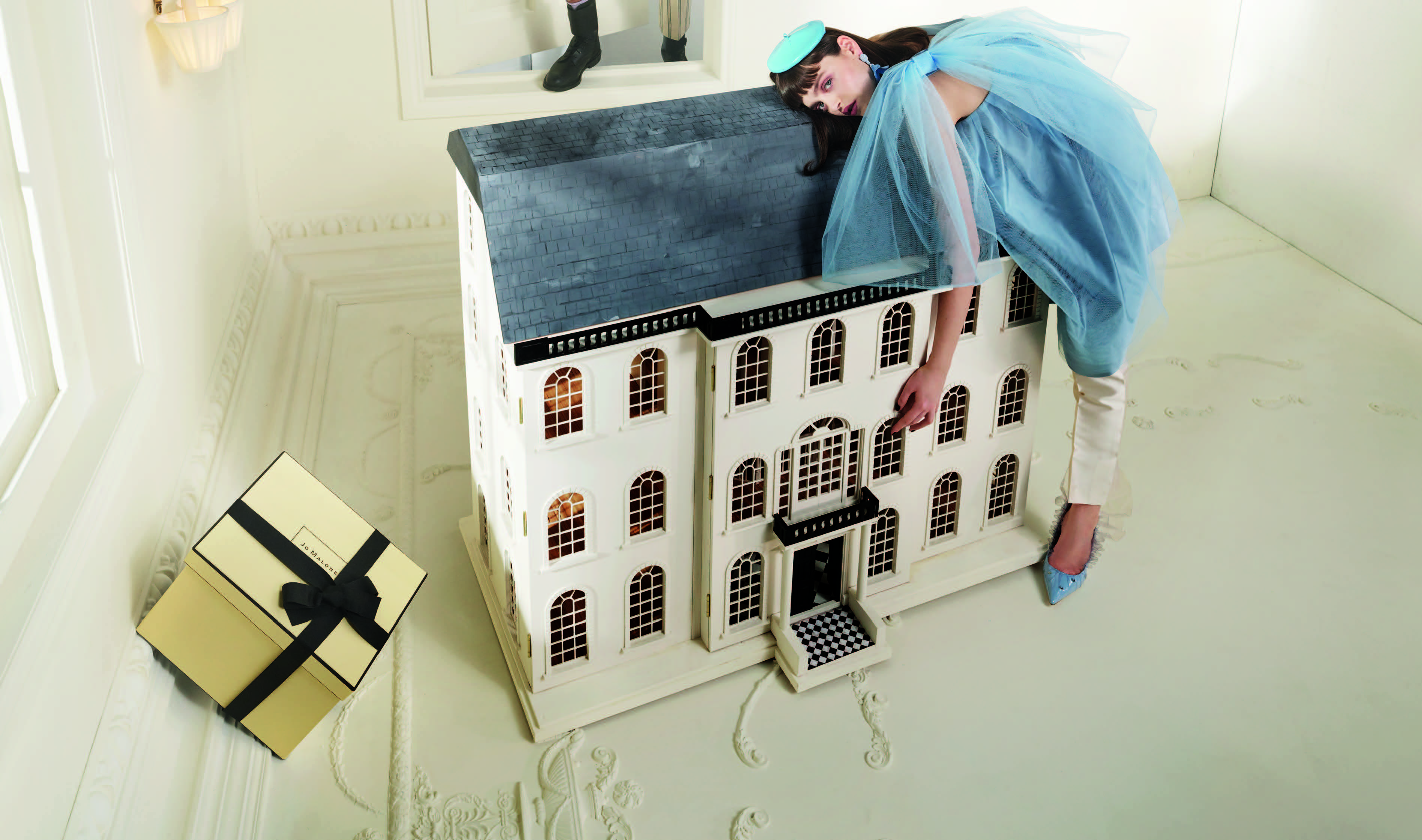 Woman in a blue dress bending over a dollhouse to promote Jo Malone opening