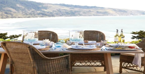 Image of a table setting against a coastal background