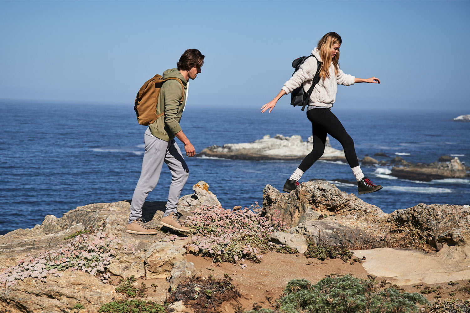 Young couple walking along the cliffs wearing UpWest apparel