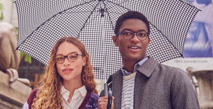 Image of young man and woman under an umbrella wearing Warby Parker glasses