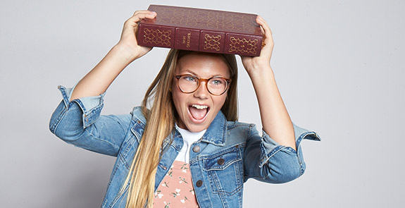 Teenage girl holding a book over her head