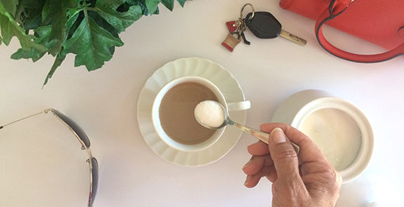A hand putting a spoonful of sugar into a coffee cup, with purse, keys, plant, and sunglasses