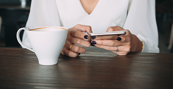 Woman texting while sitting down to coffee