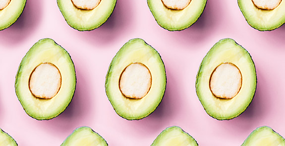 Avocado halves arranged on a pink background