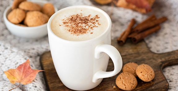 Cappuccino surrounded by cookies, cinnamon sticks, and a leaf.