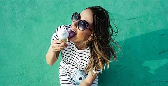 Woman eating an ice cream cone in front of a green wall