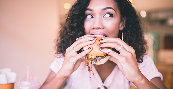 Woman eating a juicy hamburger