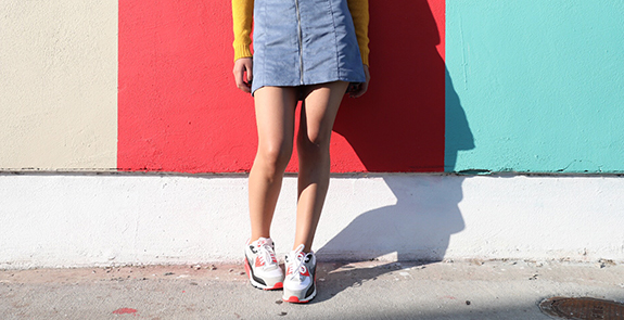 Woman's legs wearing tennis shoes, a blue skirt, and standing in front of a bright multicolored painted wall.