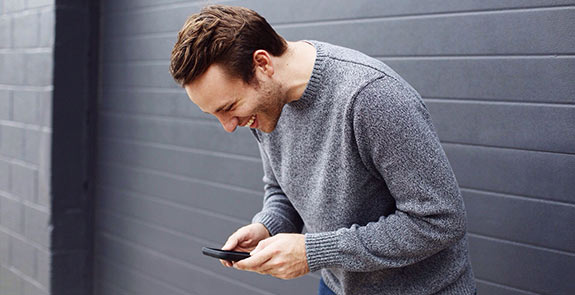 Man in a gray sweater texting