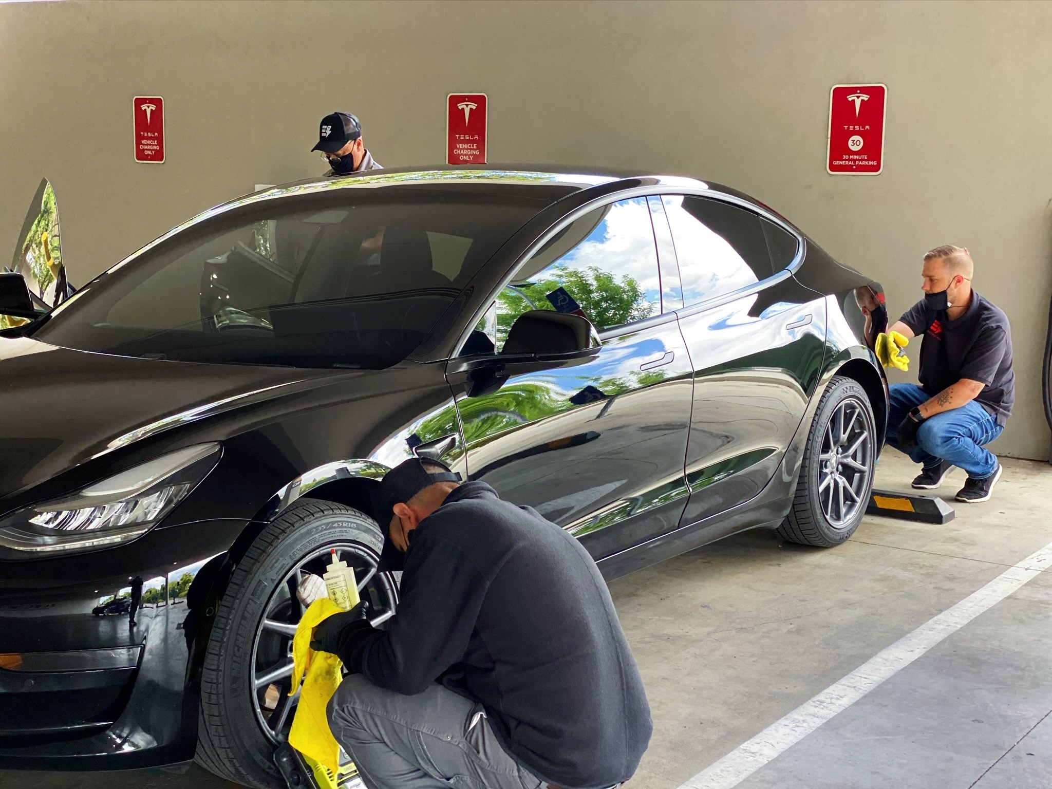 Three employees of Electric Joy cleaning a Tesla vehicle.