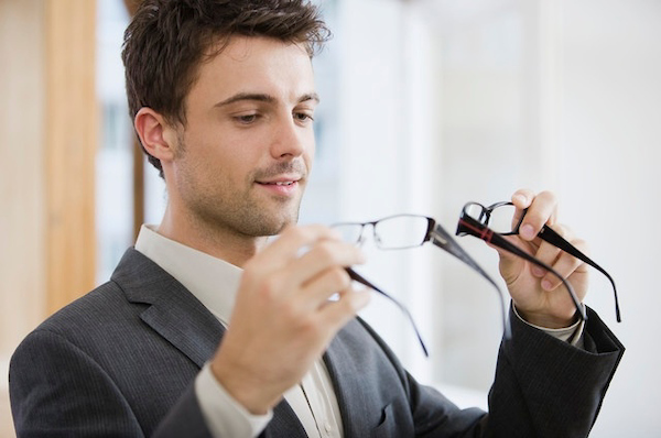 man holding two pairs of glasses and comparing them