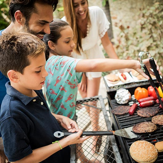 Father overseeing his family of 4 at the BBQ grill cooking food.