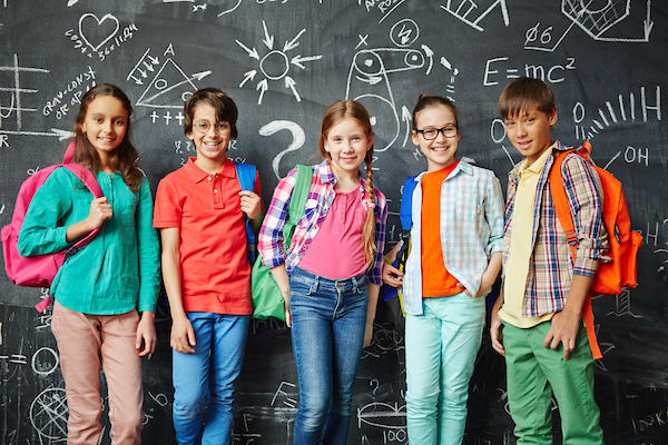a group of kids standing in front of a chalkboard carrying backpacks and smiling.