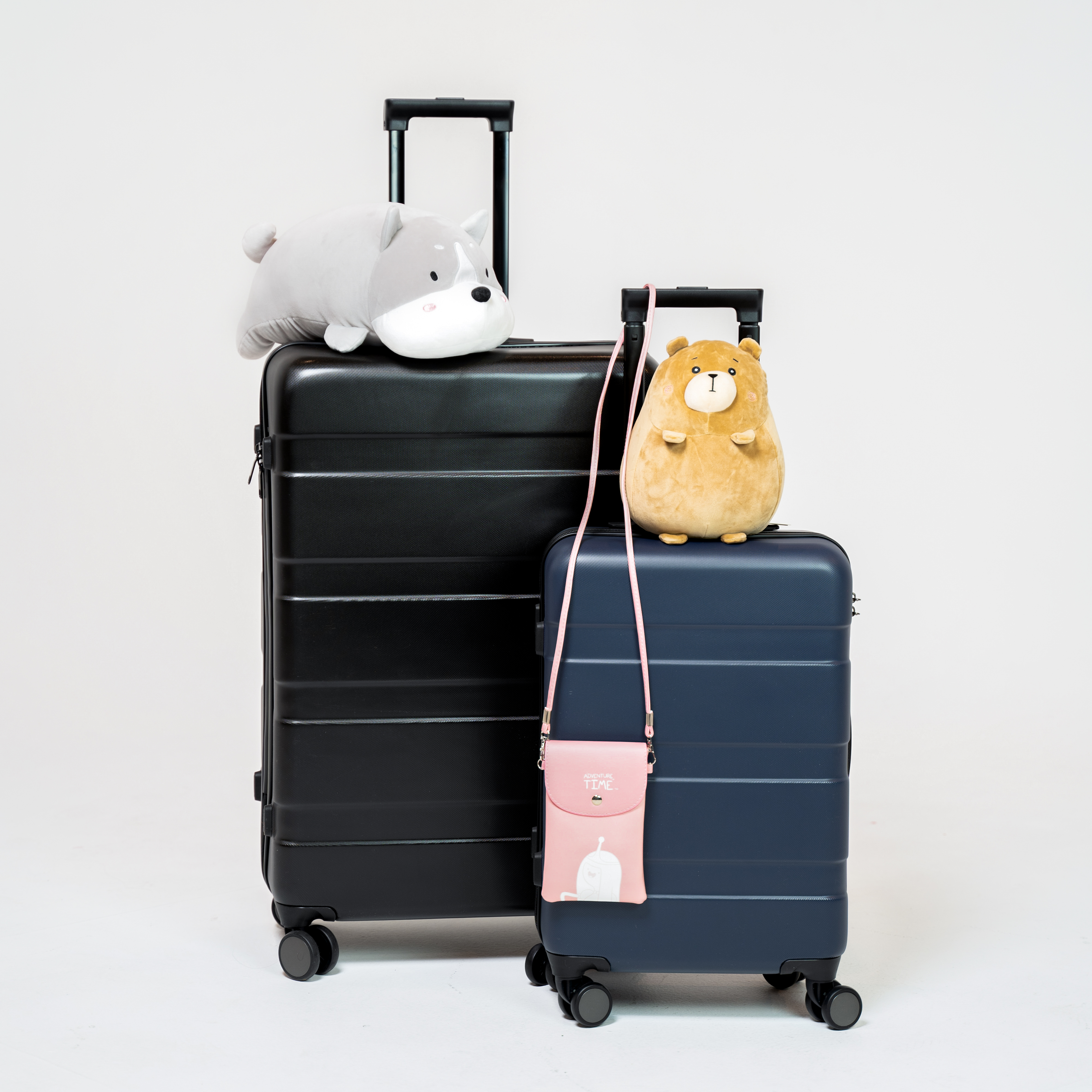 Two sizes of travel luggage.  Black and blue roller luggage on a white back ground.  Stuffed plush animals on the luggage.