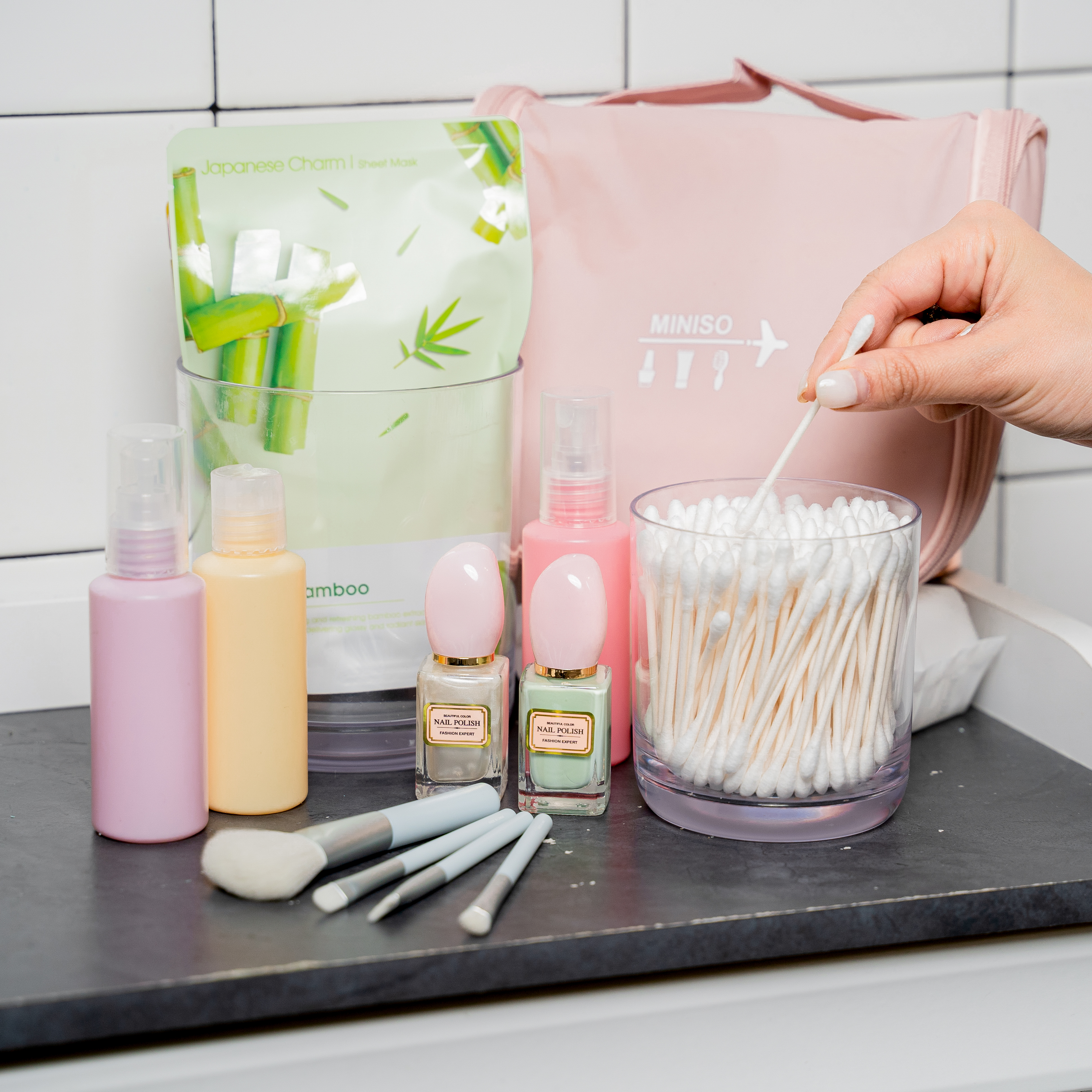 Various bottles of skin care product, cosmetic brushes, creams and q-tips on a black counter top.