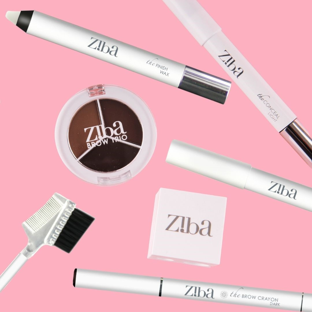 Ziba cosmetic crayons, pencils brushes and cosmetics laid out on a pink background
