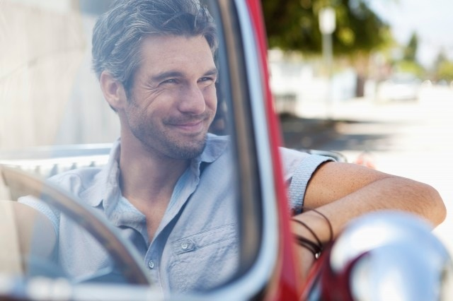 attractive man sitting in car smiling looking to the right