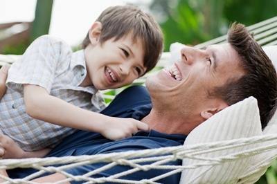 Father & son laughing laying down in a hammock.
