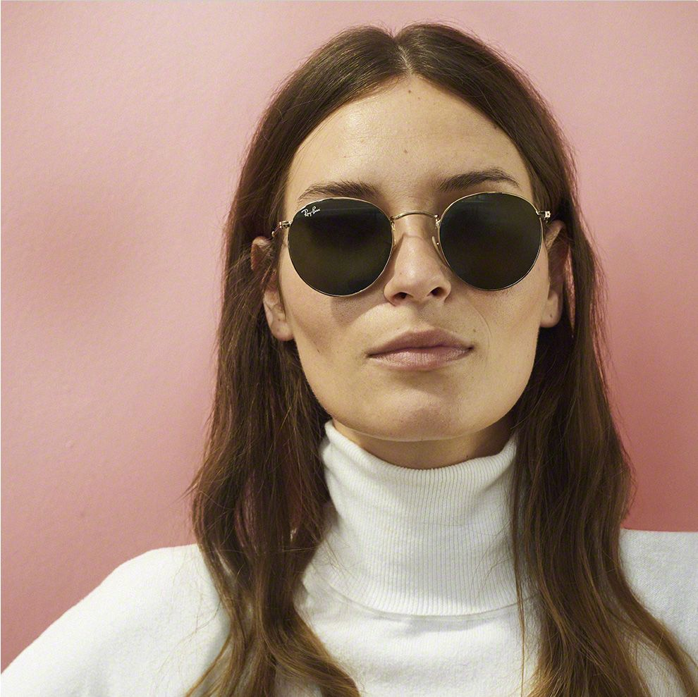 Woman with long brown hair in a white sweater wearing sunglasses