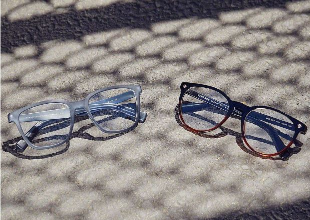 2 pairs of eyeglasses placed on cement with a shadow of a chain link fence passing over them
