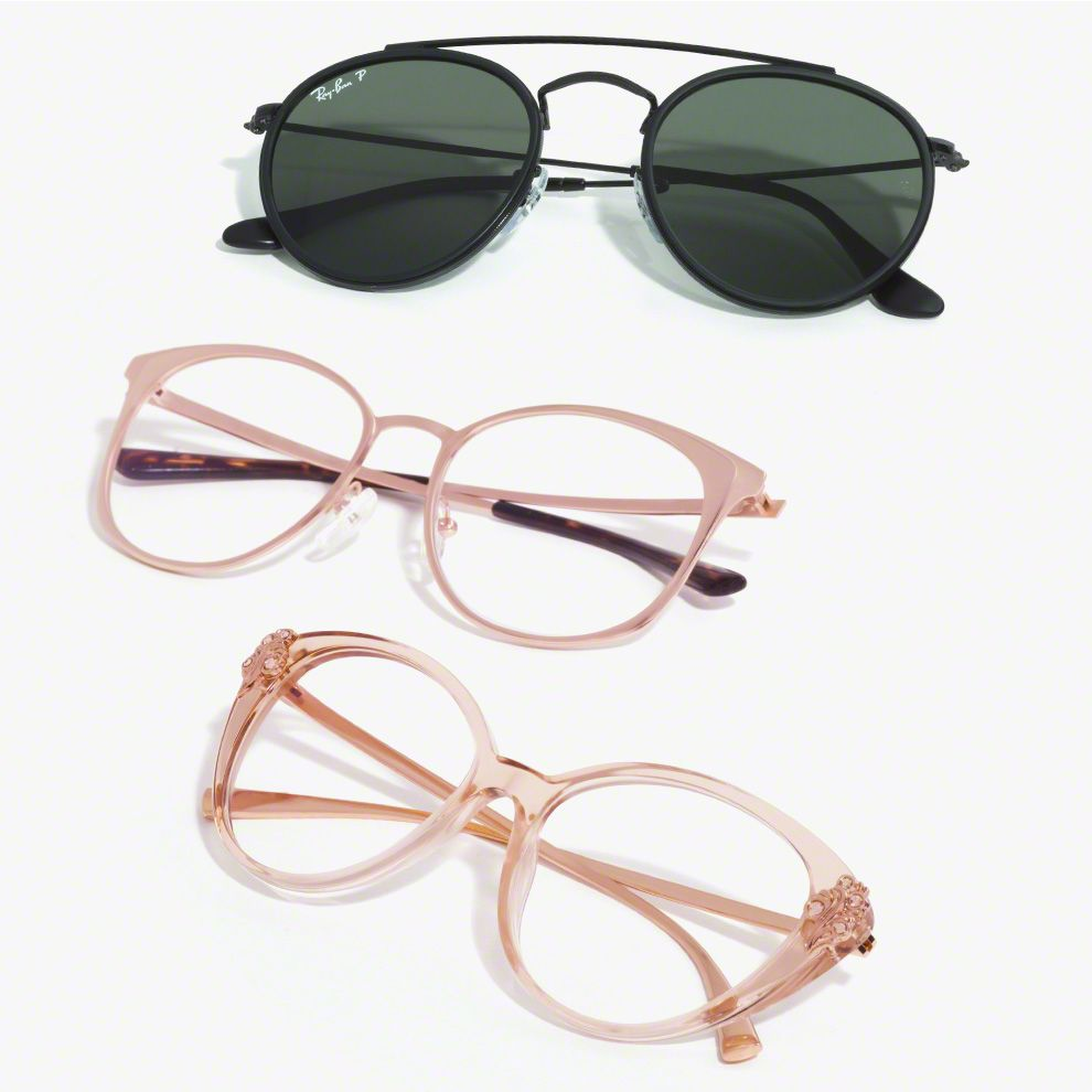 A pair of sunglasses and two pairs or prescription eyewear with rose gold frames.