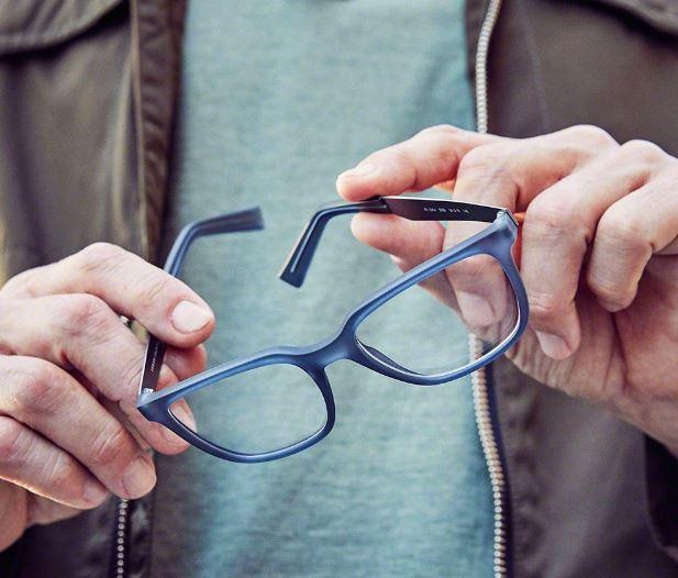 Hands holding a pair of blue eyeglass frames.
