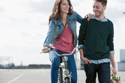 girl on bike holding onto shoulder of a guy walking with her & smiling.