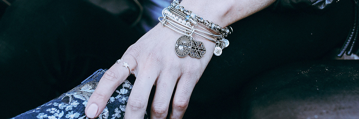 A hand wearing Alex and Ani charm bracelets and ring