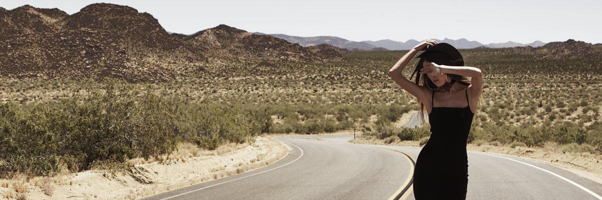 woman walking in desert wearing black dress
