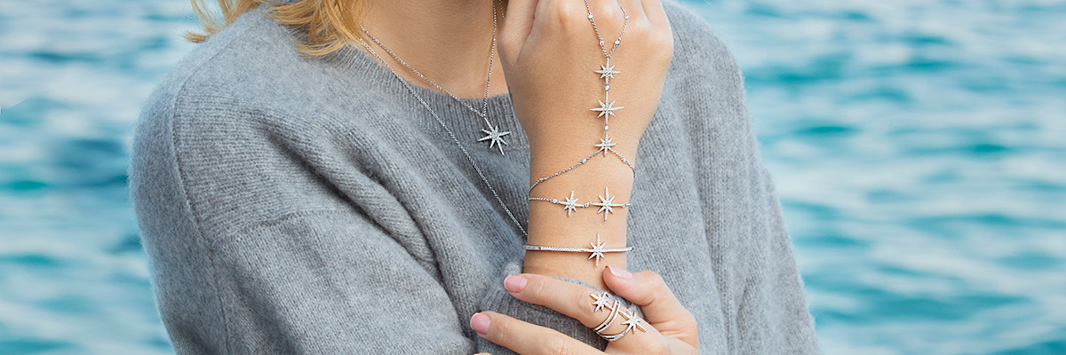 Woman wearing APM Monaco jewelry (necklace, ring, bracelets) with a star pattern.